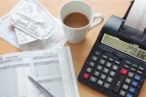 Still life bookkeeping photo of a sales ledger with a pile of re